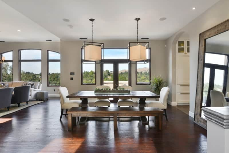 Natural light streams in through the glass paneled windows in this open dining room with cube pendants and cozy dining set over the hardwood flooring.