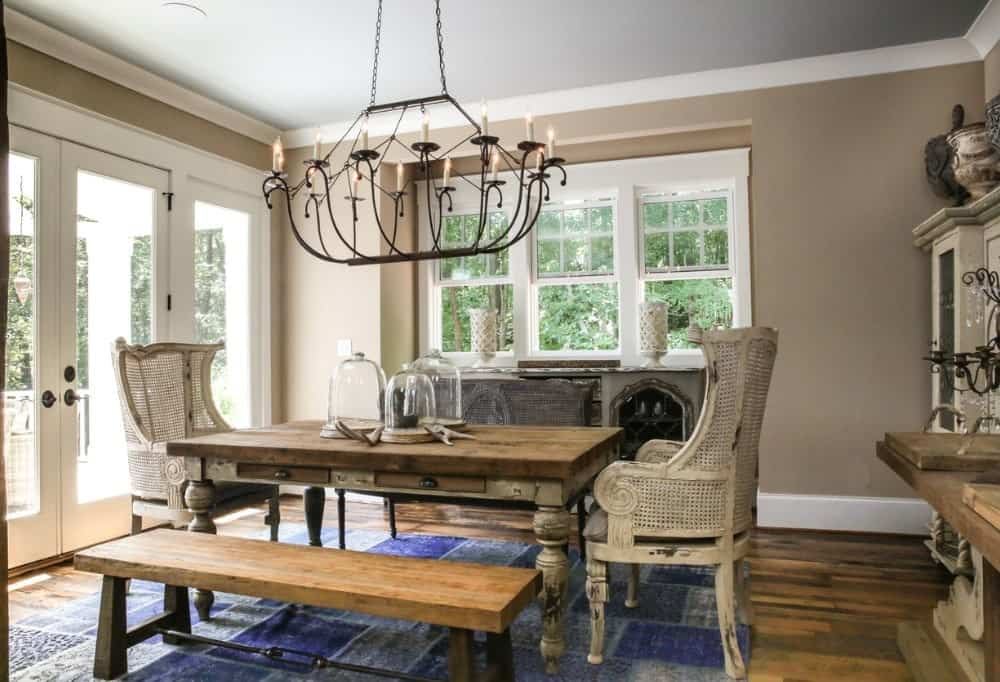 Taupe dining room with a candle chandelier and a buffet table across the rustic dining set that sits on a blue checkered rug over wood plank flooring.