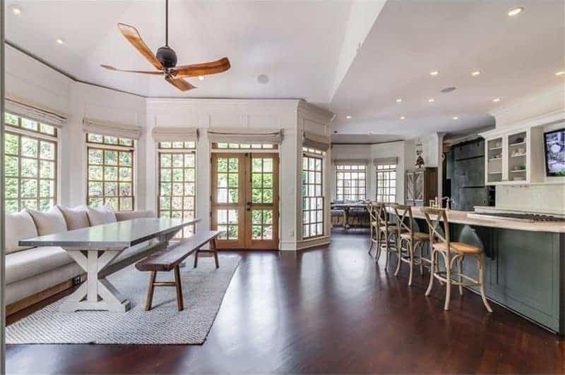 Spacious dining area across the kitchen with wooden framed windows and hardwood flooring topped by an area rug. It has a ceiling fan and a gray dining table accompanied by a wooden bench and beige sofa.