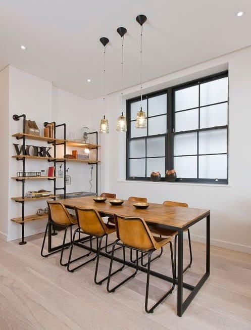 Industrial dining room features pipe shelving units matching with the wooden dining set illuminated by glass pendants and recessed ceiling lights.