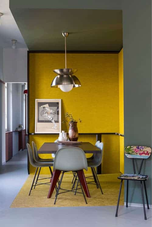 A gorgeous chair sits in front of the corner dining space highlighted by yellow walls. It has a dome pendant light along with a rectangular dining table and gray chairs.