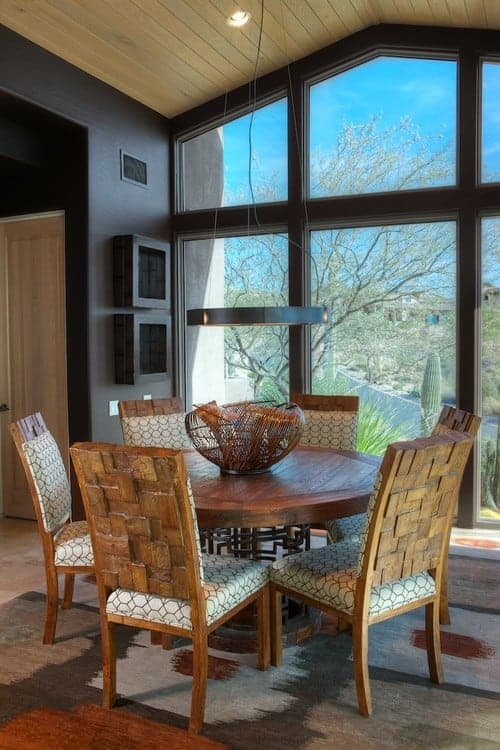 A wicker bowl sits on a round dining table surrounded with patterned chairs over a brown rug. It has full height glazing and vaulted ceiling clad in light wood planks.