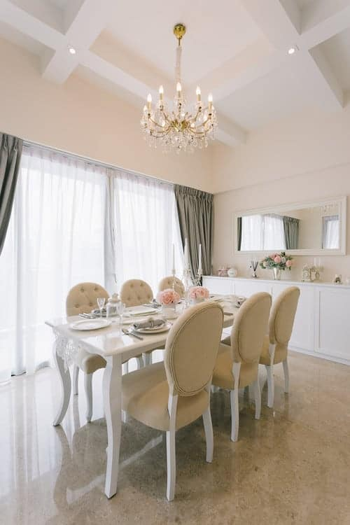 Elegant dining room with beige tufted chairs and a white dining table that matches the console table paired with a rectangular mirror. It has granite flooring and coffered ceiling with a hanging candle chandelier.