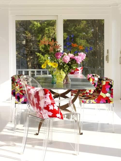 White dining room showcases a gray dining table and glass chairs accented with floral cushions and pillows that are bursting in colors.