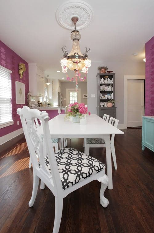 Charming dining area offers gray display cabinet and white dining set for six lighted by a gorgeous chandelier that hung from the ceiling medallion.