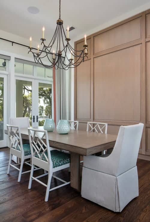 A wrought iron chandelier illuminates this transitional dining room boasting green cushioned and gray skirted chairs paired with a wooden dining table.