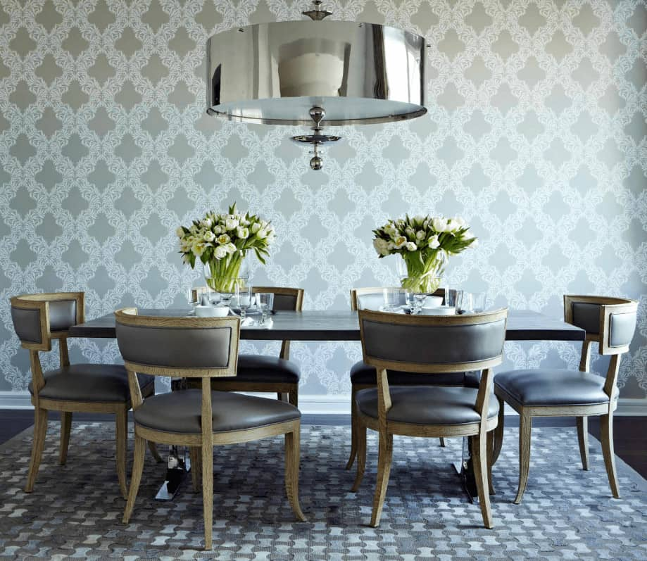 A patterned wallpaper sets an elegant backdrop in this contemporary dining room with an oversized chrome pendant light and classy dining set on an eye-catching rug.