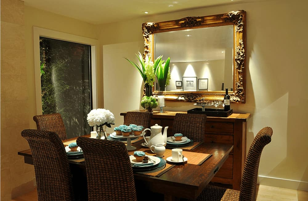 Warm dining room with wicker chairs and a wooden dining table that complements the buffet table accented by a large ornate mirror.