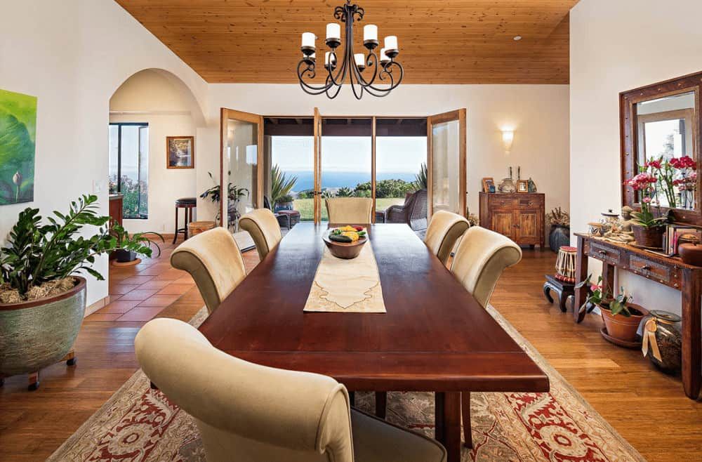 Mediterranean dining room showcases a wooden console table and matching mirror along with cozy dining set for six lighted by a wrought iron chandelier.