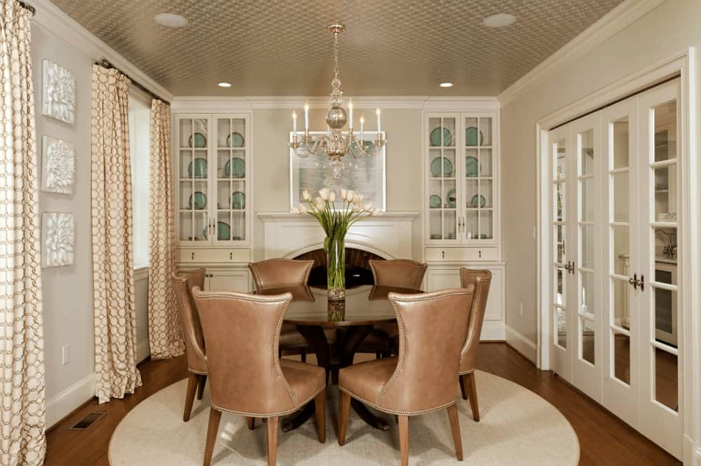 This dining room features brown leather chairs and a round dining table lighted by a candle chandelier. It includes floral artworks and white built-in cabinets with a fireplace in the middle.