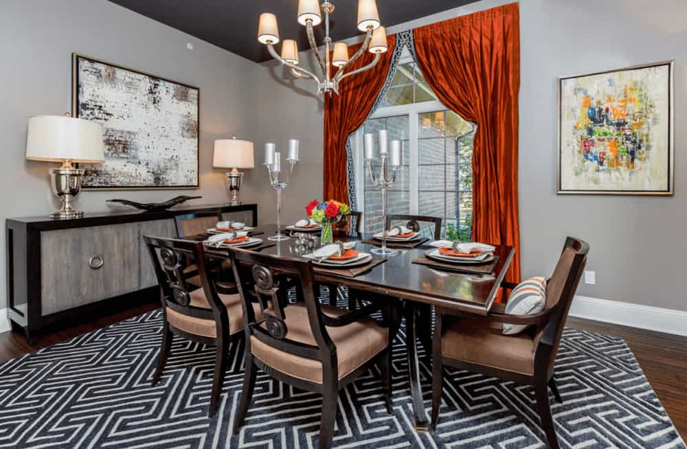 Red draperies stand out in this transitional dining room showcasing a dark wood dining set accented with a striking rug along with a black console table topped with stylish table lamps and a decorative bowl.