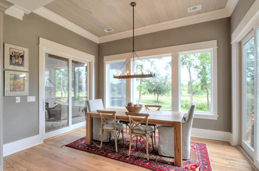 Gray dining room decorated with gorgeous artworks and a rustic chandelier that hung over the wooden dining set on a red bordered rug. It has wide plank flooring and glass paneled windows overlooking the outdoor greenery.