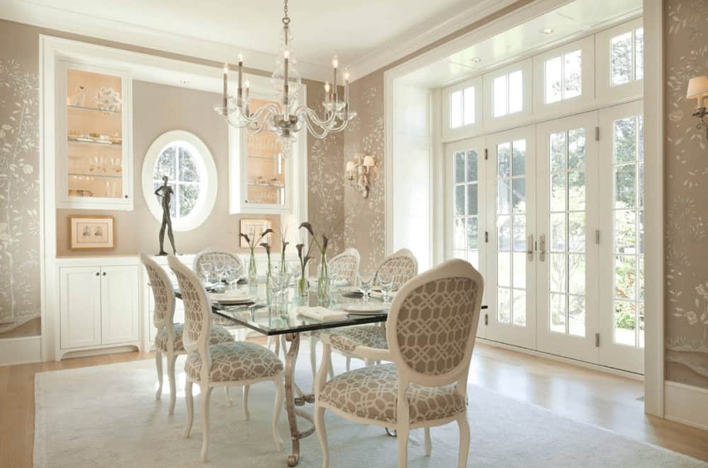 Classy dining room with a glass candle chandelier and glass top dining table accompanied by patterned round back chairs and built-in cabinets fitted on the taupe inset wall.
