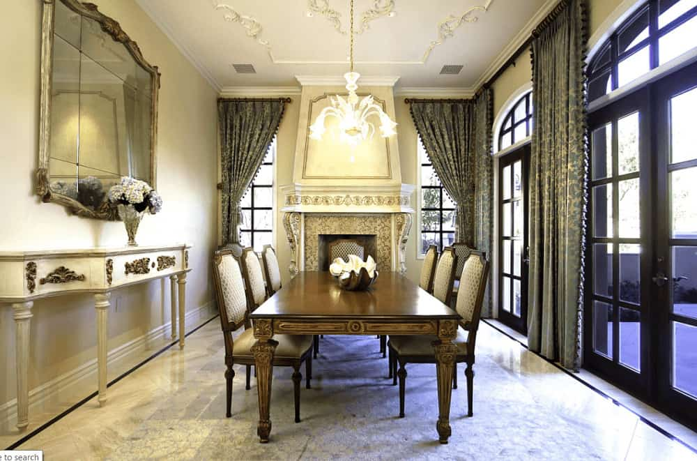 Luxury dining room boasts a gorgeous fireplace and paneled mirror mounted above the white console table. It has classy dining set for six illuminated by a glass chandelier that hung from the ornate ceiling.