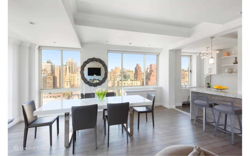 A stylish round mirror is mounted across the modern dining set in this simple dining area with wide plank flooring and glass paneled windows overlooking an incredible city view.