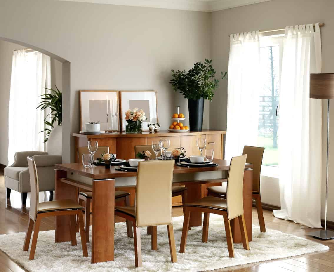 A wooden dining set compliments the buffet table topped with framed wall arts and a black vase. It has a white shaggy rug and sheer curtains covering the glazed window.