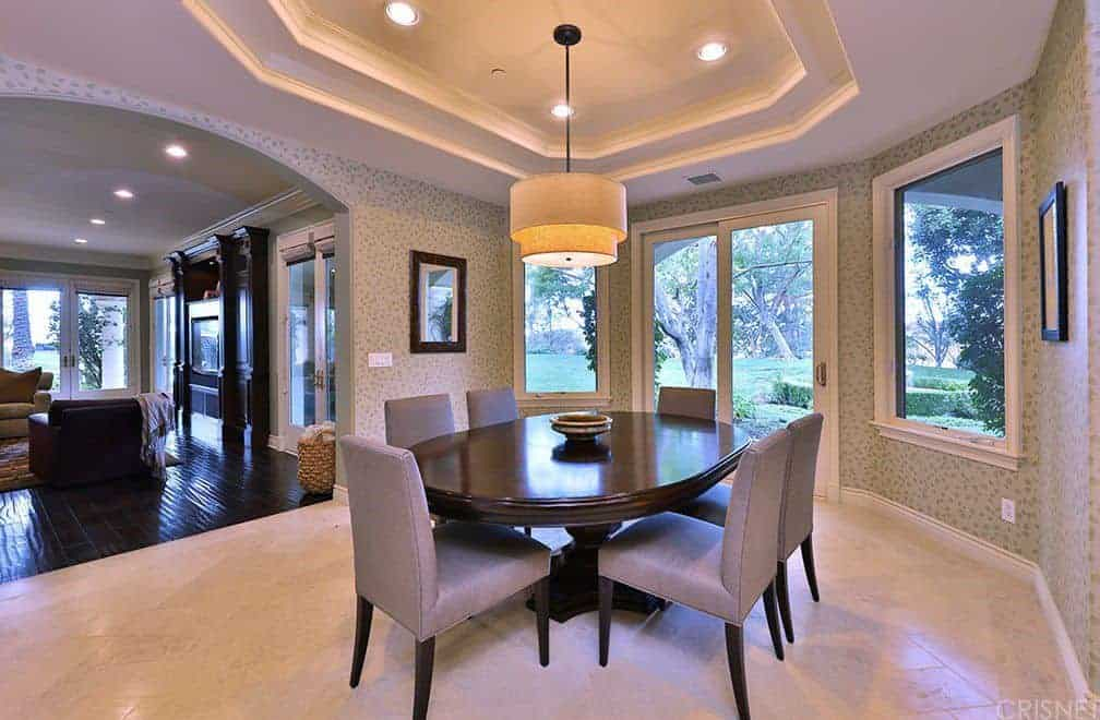 Clad in lovely wallpaper, this dining room showcases gray upholstered chairs and a dark wood dining table illuminated by a drum pendant and recessed lights fitted on the tray ceiling.