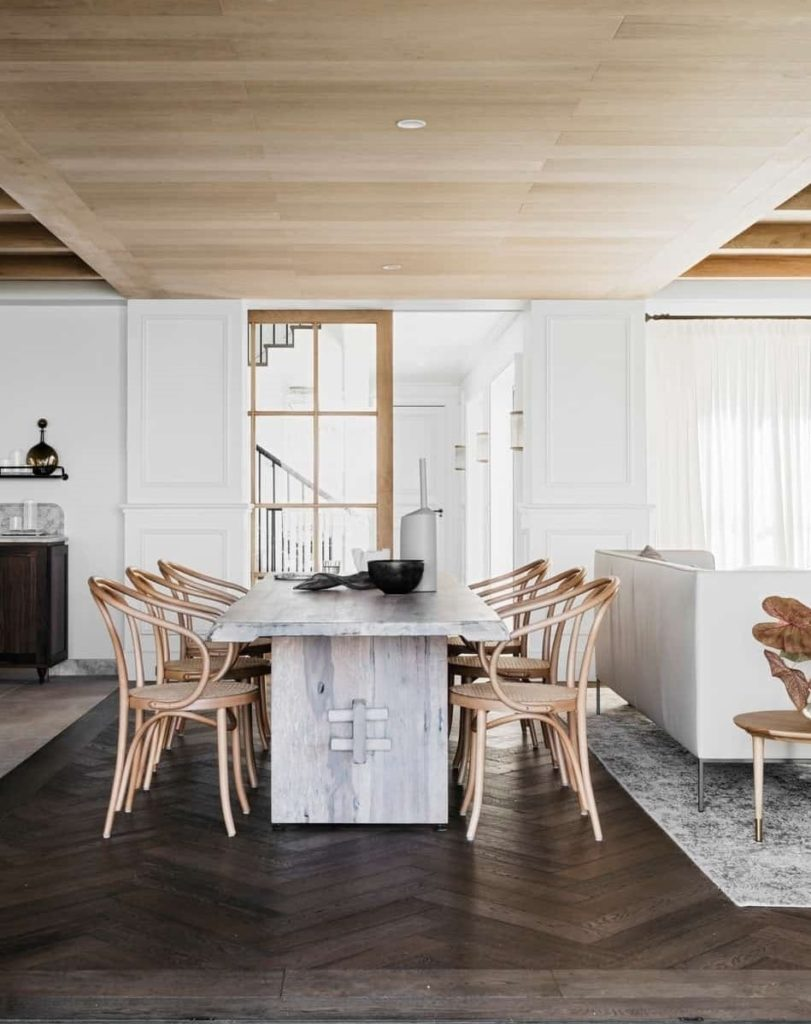 Rustic dining room with wood paneled ceiling and hardwood flooring arranged in herringbone pattern. It has a distressed dining table and round back chairs situated behind the white sofa.