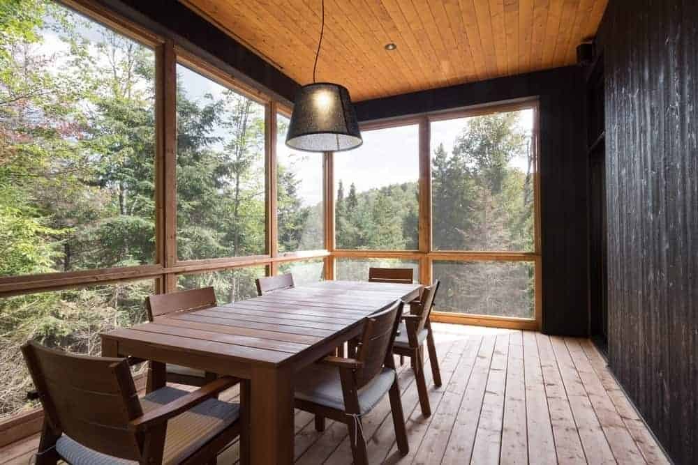 An all wood dining room features wide plank flooring that complements the wooden dining set and ceiling for a cohesive look. It is enclosed in a black wall and a panoramic window overlooking the enchanting forest.