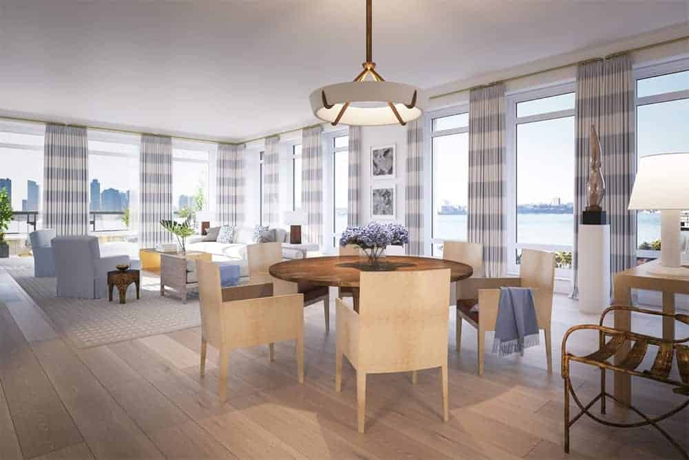 An open dining area offers light wood chairs and a round dining table illuminated by a white pendant along with natural light that flows in through the glass paneled windows.