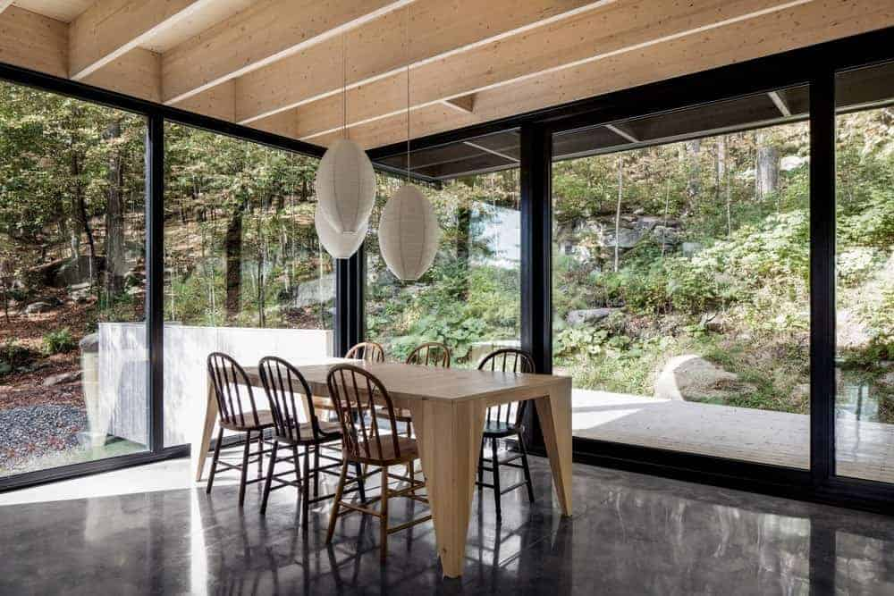 Full height glazing with a majestic forest view creates an alfresco dining feel in this airy dining room with a light wood plank table for six lighted by white pendants that hung from the beamed ceiling.