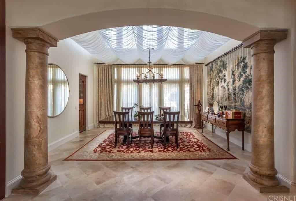 A pair of large columns form an archway leading us to this classic dining room with a round mirror and buffet table that complements the wooden dining set on a red bordered rug.