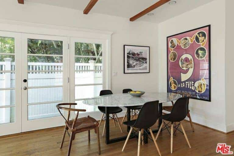 This dining room boasts black framed wall arts and a marble top dining table surrounded by black modern and wooden round back chairs. It has hardwood flooring and white ceiling lined with wood beams.