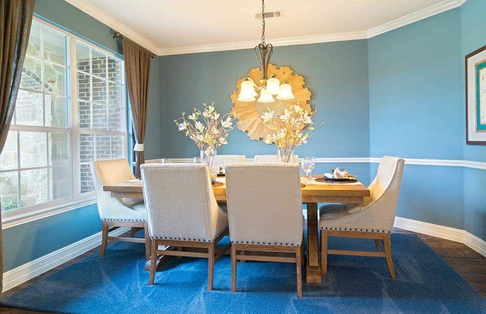 Blue dining room decorated with a sunburst mirror and a vintage chandelier that hung over the wooden dining table paired with beige upholstered chairs.