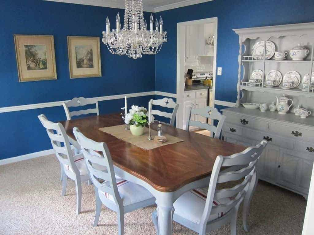This dining room is furnished with a wooden dining table for six and a white cabinet displaying ceramic dinnerware. It has carpet flooring and blue walls mounted with framed photos.