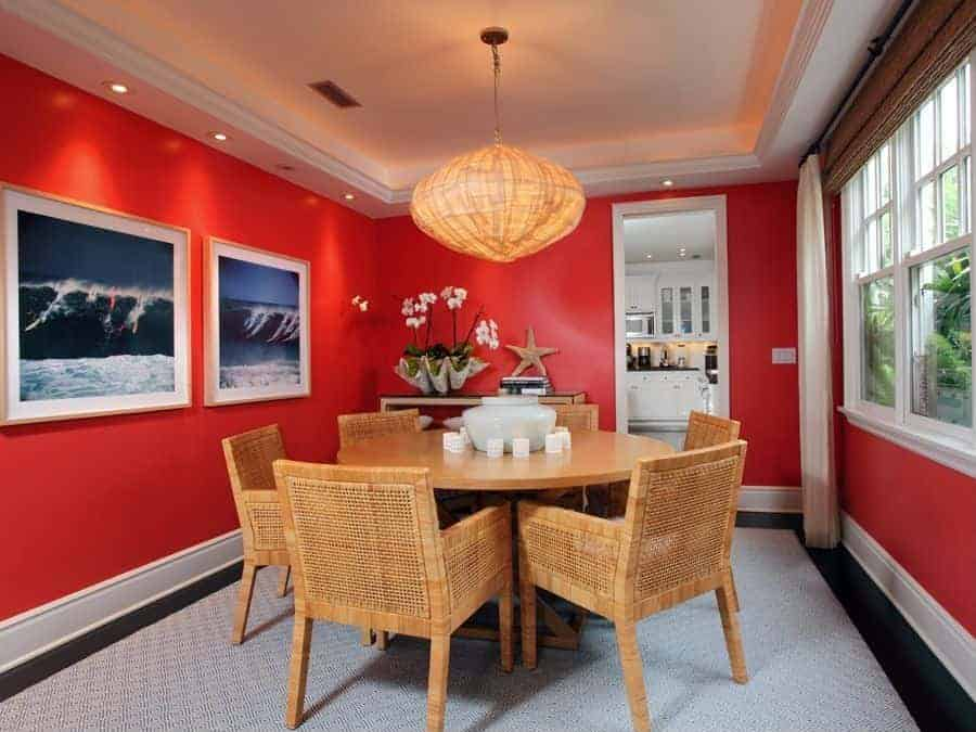 Red dining room designed with wave wall arts and a rattan pendant light that complements the wicker chairs surrounding a wooden dining table. It has a tray ceiling and black flooring topped by a gray rug.