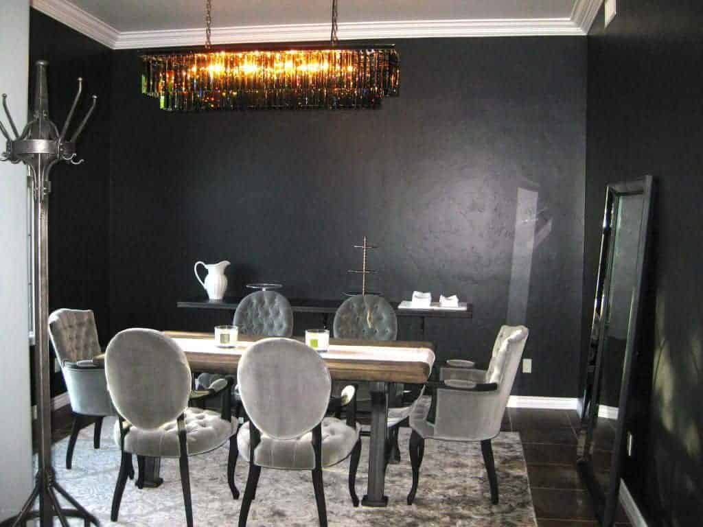Black dining room showcases gray tufted chairs and a natural wood dining table lined with a white runner. It includes a fancy linear chandelier, a large mirror and a buffet table that blends in with the wall.