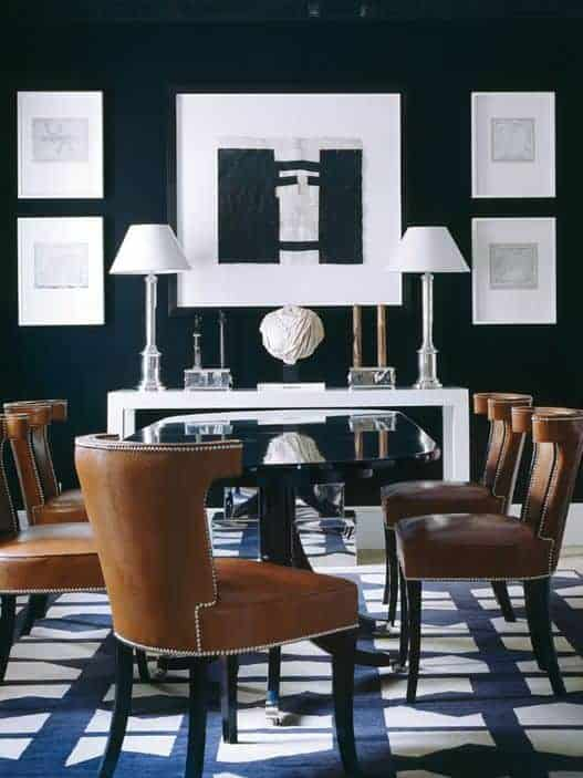 White lampshades sit on a sleek console table in this dining room with gallery frames and a glass top dining table for six that sits on an eye-catching blue rug.