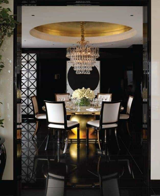 Deluxe dining room illuminated by a cascading crystal chandelier that hung from the round tray ceiling. It has a gorgeous dining table and white upholstered chairs contrasted with black walls and tiled flooring.