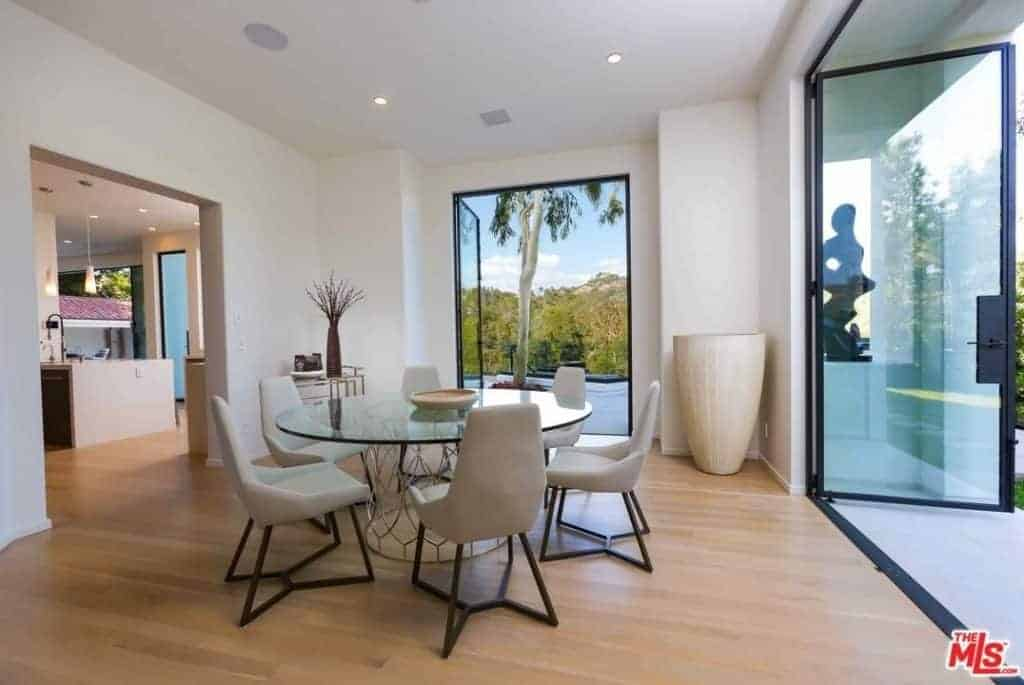 Gray upholstered chairs sit at a stylish round dining table in this airy dining room with light hardwood flooring and glass doors that open to the lush green yard.