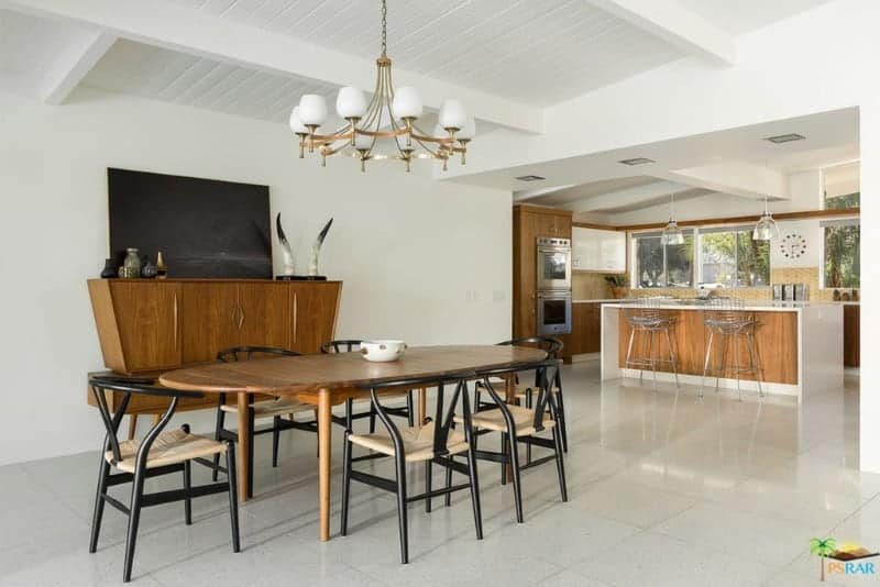 An open dining area offers a wooden dining set and a stylish console table topped with a horn decor and black canvas. It is lighted by a brass chandelier that hung from the beamed ceiling.