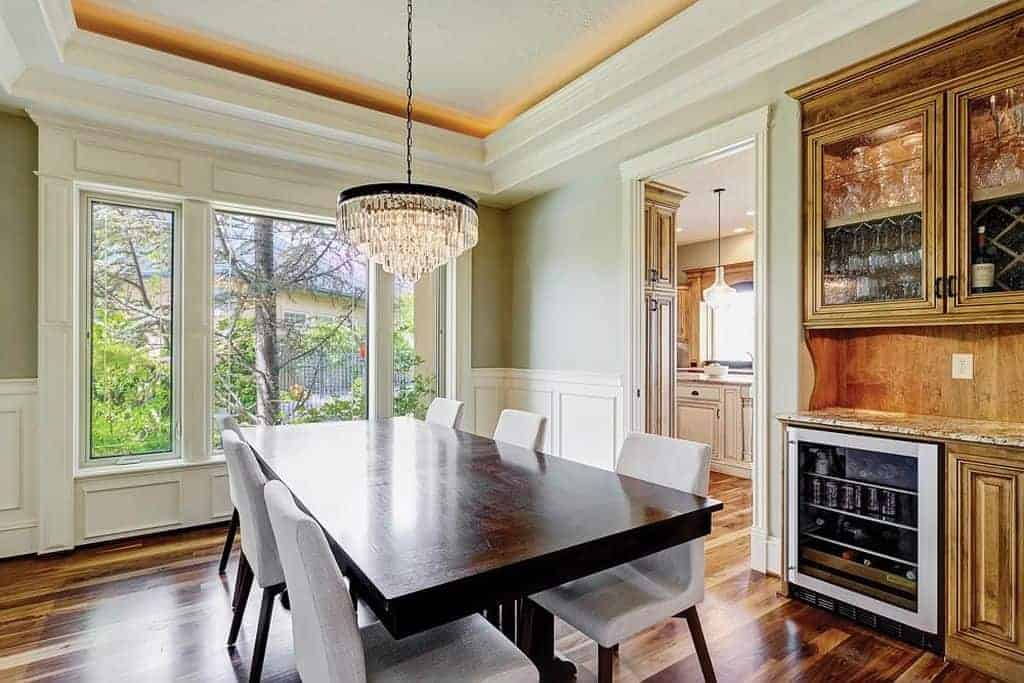 A fancy chandelier illuminates this dining room showcasing a dark wood dining table and gray upholstered chairs. There's a front glass cabinet on the side integrated with a beverage fridge and marble countertop.