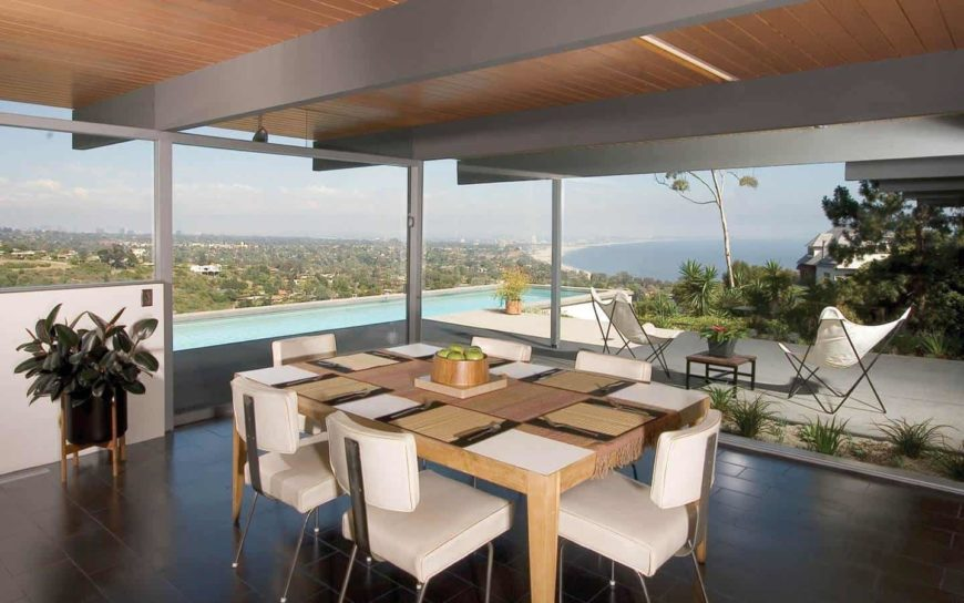 This dining room offers white cushioned chairs and a wooden dining table covered in tasseled runner and wicker placemats. It is surrounded by panoramic windows overlooking the stunning outdoor scenery.