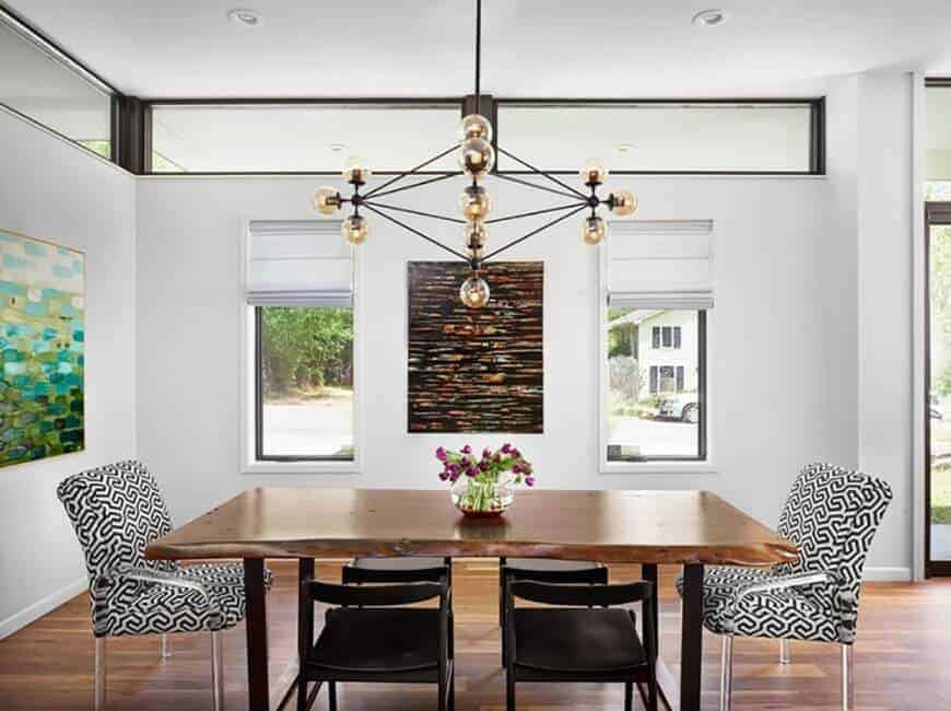 A contemporary chandelier illuminates this dining room showcasing gorgeous artworks and a smooth wooden dining table paired with black and patterned armchairs.