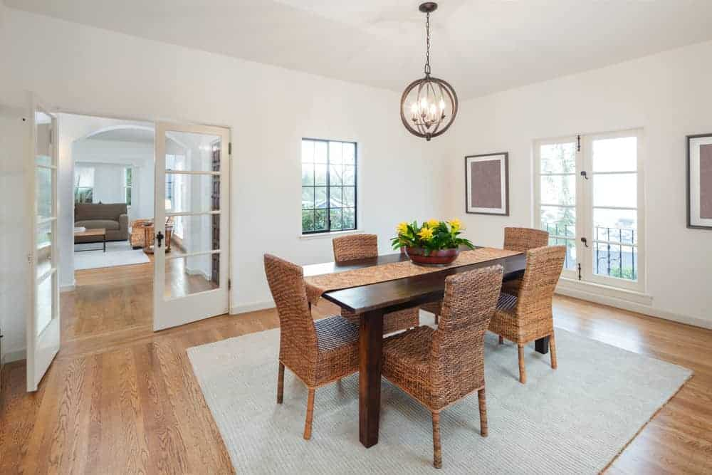 White dining room with a spherical chandelier and dark wood dining table surrounded by wicker chairs on a gray area rug. It has hardwood flooring and French doors leading out to the foyer and balcony.