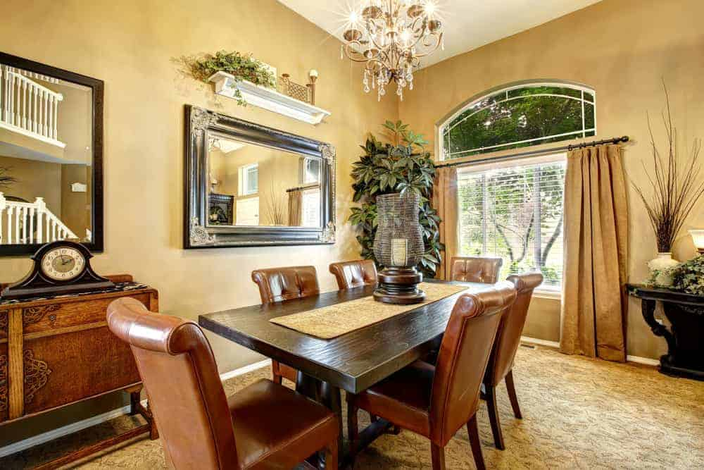 Yellow dining room boasts a brass chandelier and framed mirror mounted below the white floating shelf. It has tufted leather chairs and a rectangular dining table topped with a runner and a large candle holder.