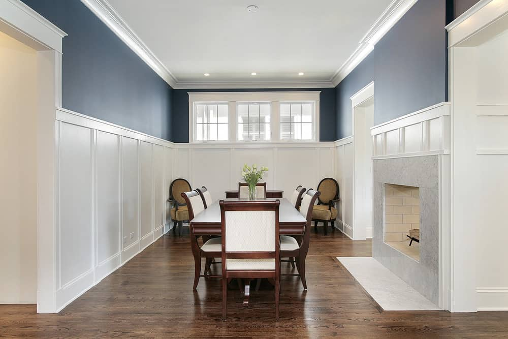 Formal dining room with hardwood flooring and deep blue walls dominated by white wainscoting. It includes a fireplace and a seating area placed across the wooden dining set.