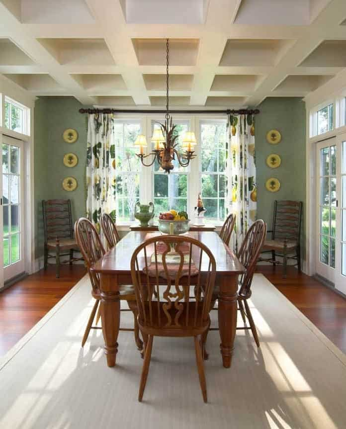 Fresh dining room surrounded with white framed windows that bring plenty of natural light in. It has round wall arts and a wooden dining set for six illuminated by a vintage chandelier that hung from the coffered ceiling.