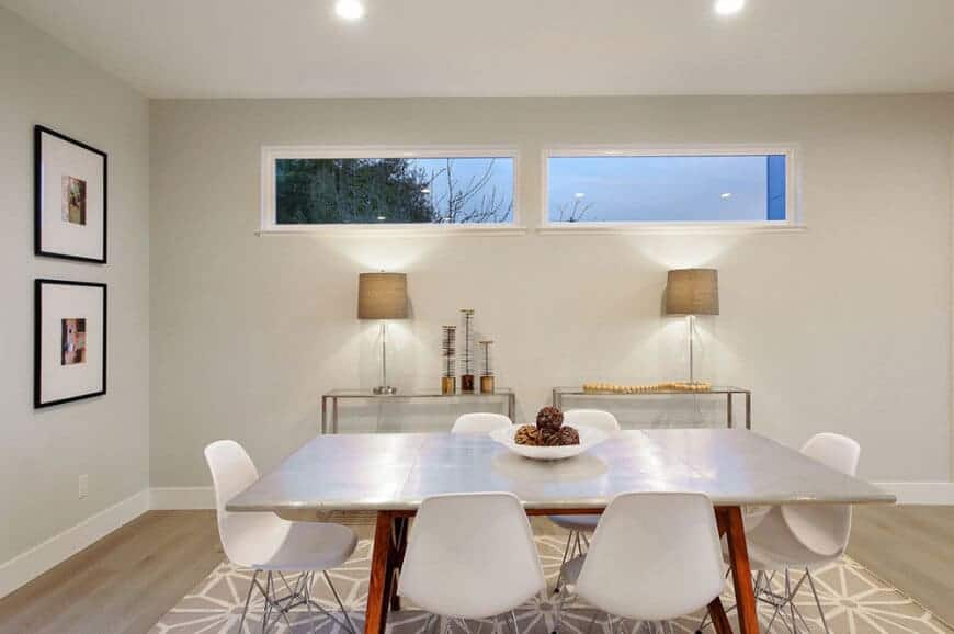 Traditional lampshades with chrome bases sit on a glass top table in this white dining room featuring black framed wall arts and a dining table for six on an eye-catching rug.