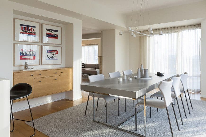 This dining room is designed with white pendant lights and gallery frames mounted above the floating cabinet. It has a gray dining table and stylish chairs blending in with the area rug.