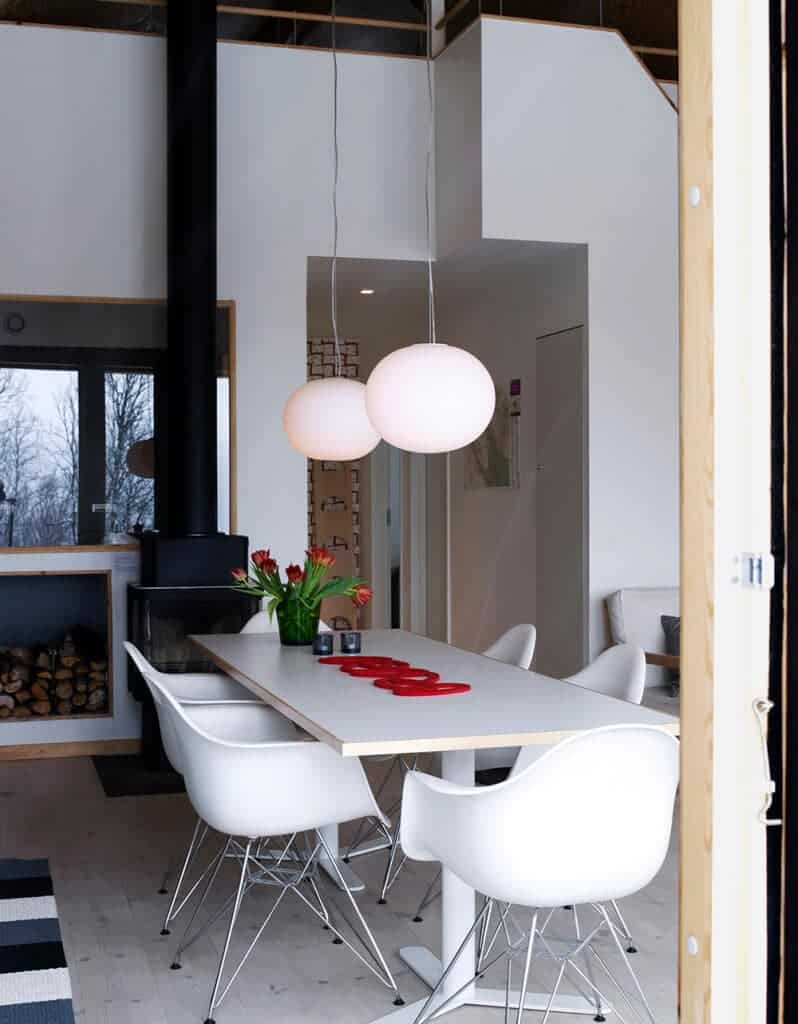 Contemporary dining room features a freestanding fireplace and white modern chairs surrounding a rectangular dining table lighted by a pair of frosted glass globe pendants.