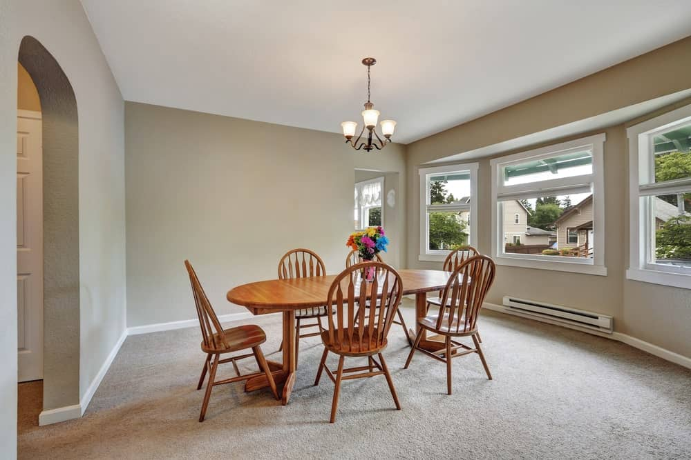 Simple dining room with carpet flooring and glass paneled windows inviting natural light in. It has a wrought iron chandelier and wooden dining set for six accented with colorful flowers.