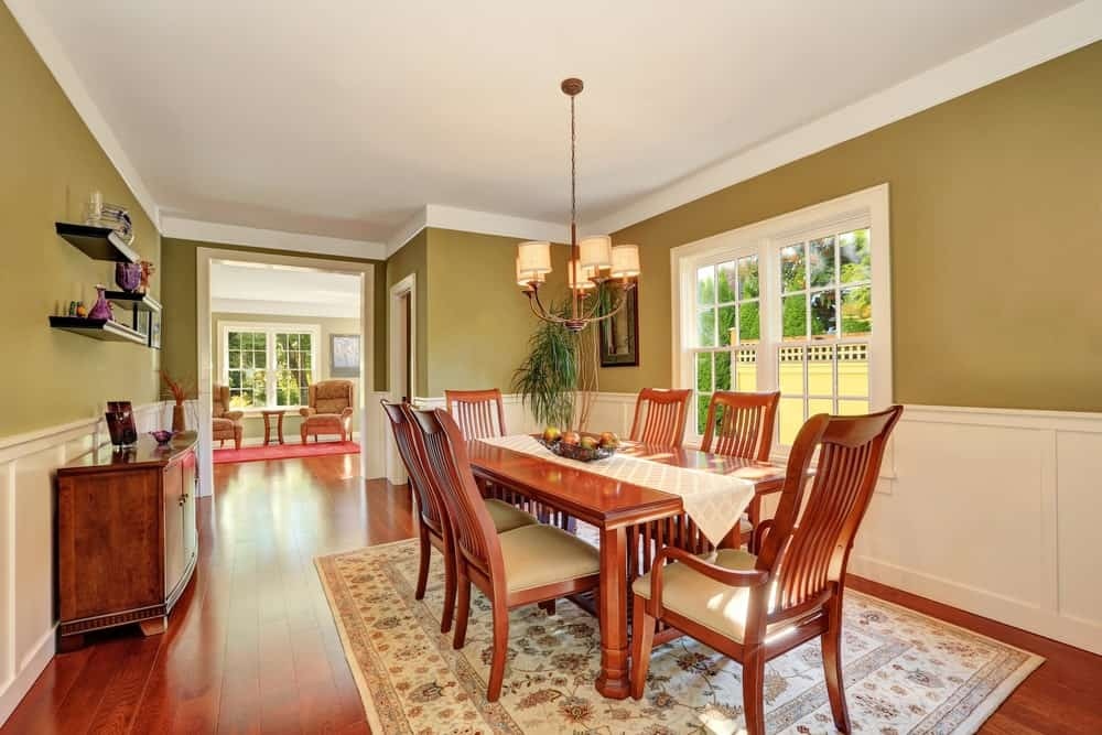 A potted plant in the corner creates a refreshing ambiance in this green dining room offeringa wooden dining table for six that sits on a floral area rug lighted by a copper chandelier.