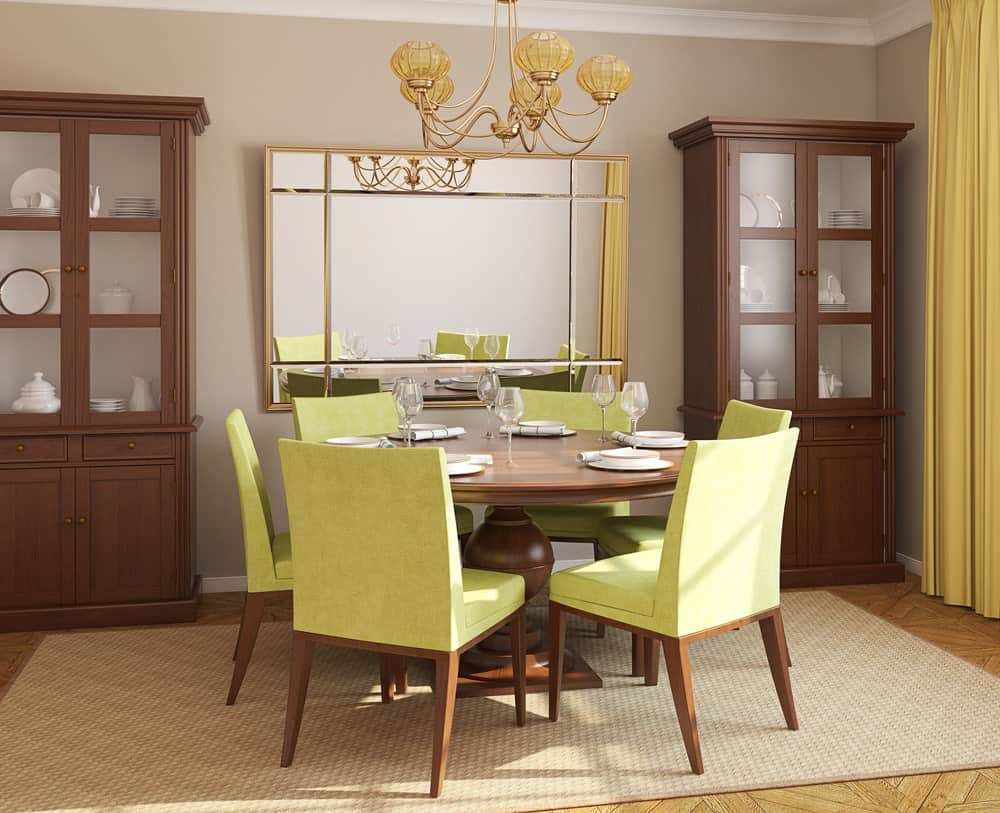 This dining room is designed with a brass chandelier and gorgeous mirror flanked by wooden display cabinets. It has a round dining table and green cushioned chairs that sit on a textured area rug.