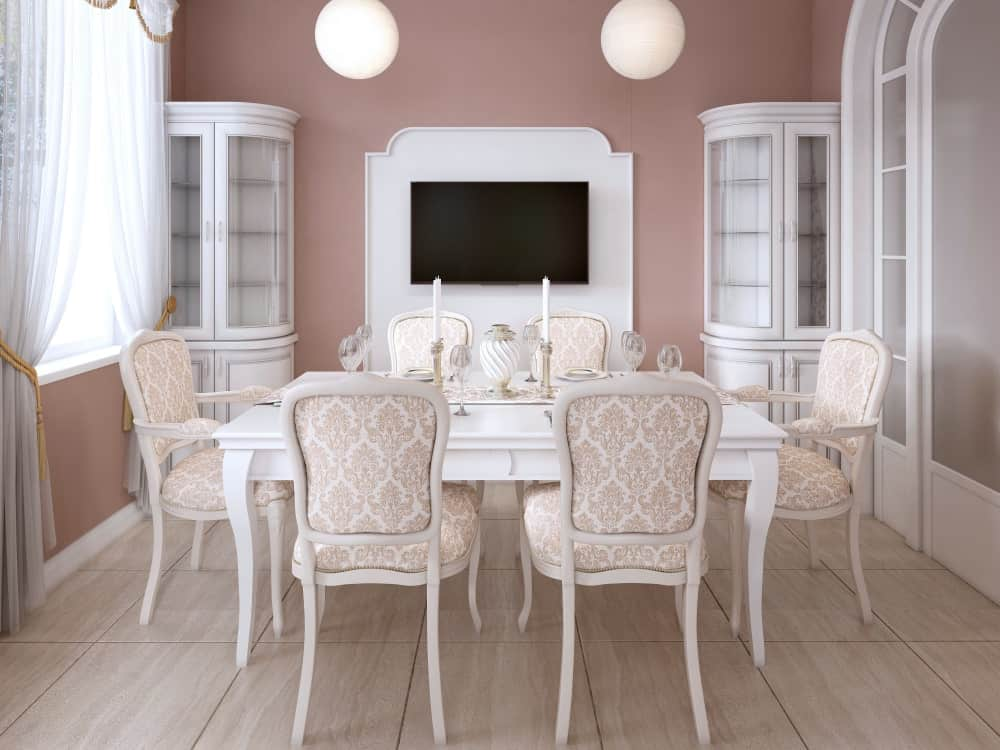 Pink dining room with wall-mounted TV, a window, and a dining table for six.