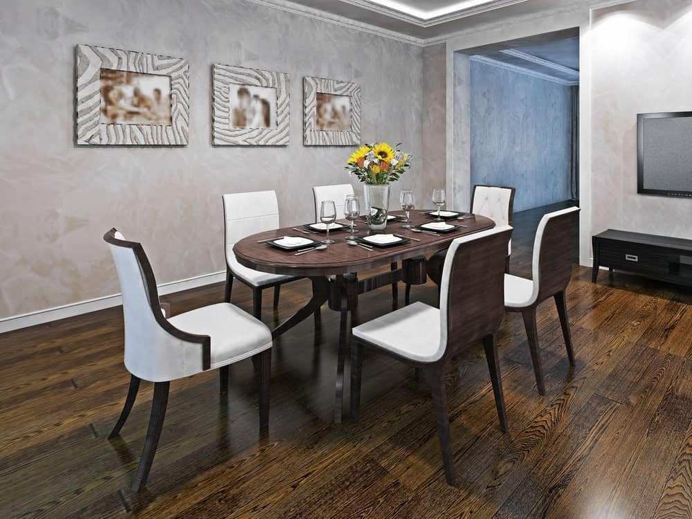 White upholstered chairs sit at an oval dining table in this simple dining area with hardwood flooring and concrete walls mounted with lovely framed photos.